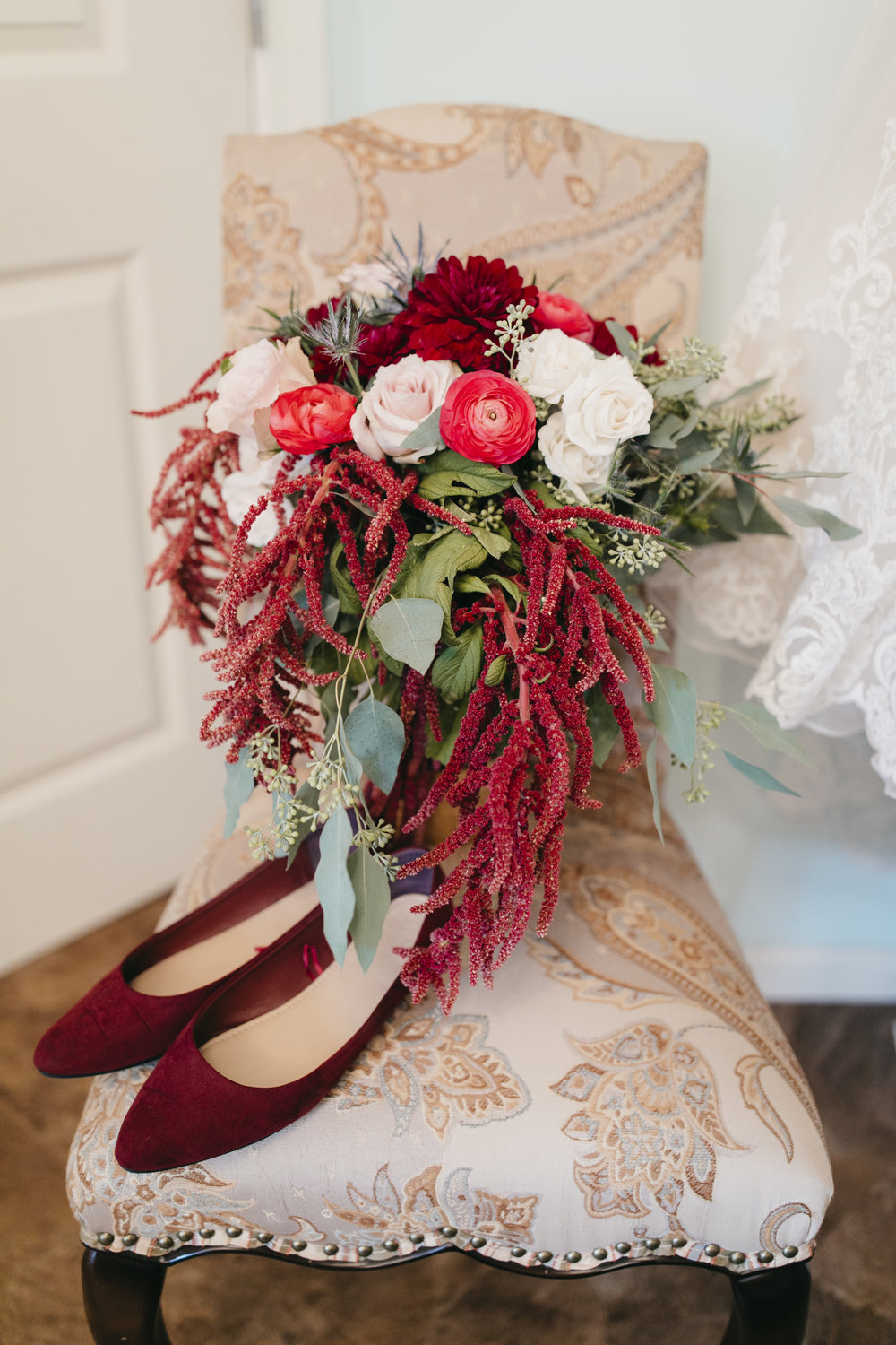 The season and rich colors were also referenced in the beautiful floral arrangements, which included seeded eucalyptus, ranunculus, carnations, roses, and thistle. -